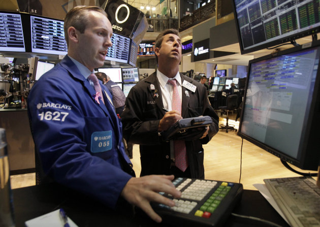 FILE- In this Wednesday, July 18, 2012, file photo, trader William Sachs, right, check prices as he works on the floor of the New York Stock Exchange. A new sign of recovery in the housing market and strong corporate earnings sent stocks higher on Wednesday.(AP Photo/Richard Drew, File)