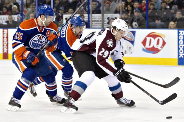 Colorado Avalanche's Nathan MacKinnon (29) is chased by Edmonton Oilers' Nick Schultz (15) and Justin Schultz (19) during first-period NHL hockey game action in Edmonton, Alberta, Thursday, De