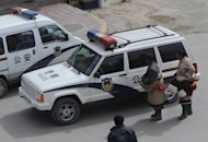 Two Tibetan Buddhist pilgrims look at a police car outside the Labrang Monastery in Xiahe, Gansu Province. A Tibetan man has died after setting himself on fire in northwest China, state media and rights groups said, in the fourth self-immolation in the region in less than a week