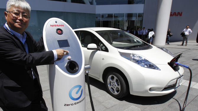 Nissan Motor Co. chief vehicle engineer Hidetoshi Kadota demonstrates a quick charge of a Nissan Leaf by a solar-assisted EV charging system at Nissan's global headquarters in Yokohama, Monday, July 11, 2011. Nissan is testing a super-green way to recharge its Leaf electric vehicle using solar power, part of a broader drive to improve electricity storage systems. In the new charging system, electricity is generated through 488 solar cells installed on the roof of the Nissan headquarters building. Four batteries from the Leaf had been placed in a box in a cellar-like part of the building, and store the electricity generated from the solar cells, which is enough to fully charge 1,800 Leaf vehicles a year, according to Nissan. (AP Photo/Koji Sasahara)