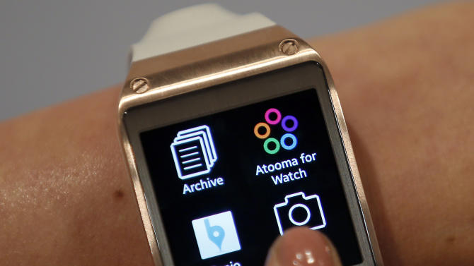 FILE - In this Wednesday, Sept. 4, 2013, file photo, a model touches the screen of a Samsung Galaxy Gear smartwatch in Berlin, Germany. The so-called smartwatch is what some technology analysts believe could become this year's must-have holiday gift. (AP Photo/Michael Sohn, File)