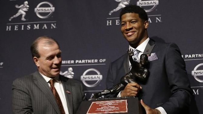 Florida State quarterback Jameis Winston, right, stands with FSU coach Jimbo Fisher while holding the Heisman Trophy after winning the award on Saturday, Dec. 14, 2013, in New York