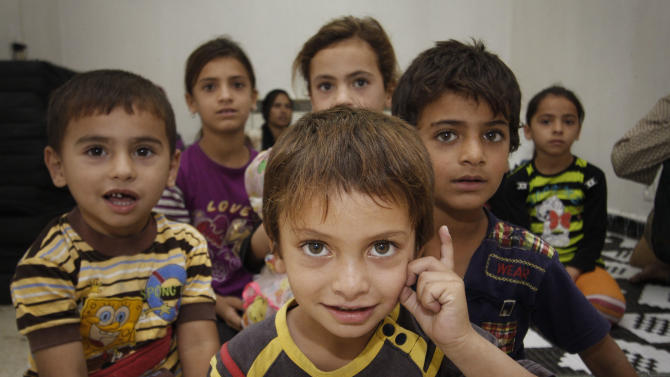 Syrian children, who fled their homes with their families due to fighting between Syrian rebels and government forces, take refuge at the Samiya al-Makhzumi school in Mezzeh neighborhood, in Damascus, Syria, Sunday, Sept. 16, 2012. Many Syrians who have fled violence in their country are living near the border but outside the dozen camps, either staying with relatives, renting apartments, and in some cases take refuge at schools. The influx since the uprising against Syrian President Bashar Assad began 18 months ago has raised concerns about sectarian tension and militant activity in the region. (AP Photo/Muzaffar Salman)