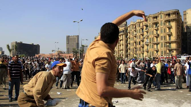 A protester throws a stone after scuffles broke out between groups of several hundred protesters in Tahrir square when chants against the new Islamist president angered some in the crowd in Cairo, Egypt, Oct. 12, 2012. The scuffles between supporters and opponents of President Mohammed Morsi reflect deep political divisions among the country's 82 million people, more than a year after the popular uprising that toppled Hosni Mubarak. (AP Photo/Khalil Hamra)