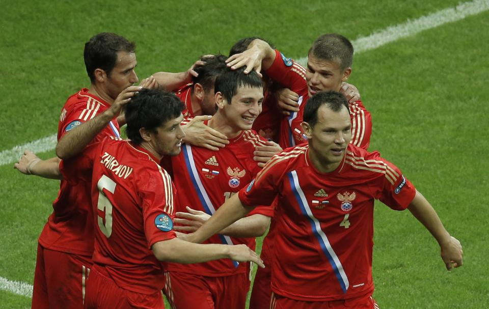 Russia's Alan Dzagoyev, center, is congratulated by his teammates after scoring the opening goal during the Euro 2012 soccer championship Group A match between Poland and Russia in Warsaw, Poland, Tuesday, June 12, 2012. (AP Photo/Gero Breloer)