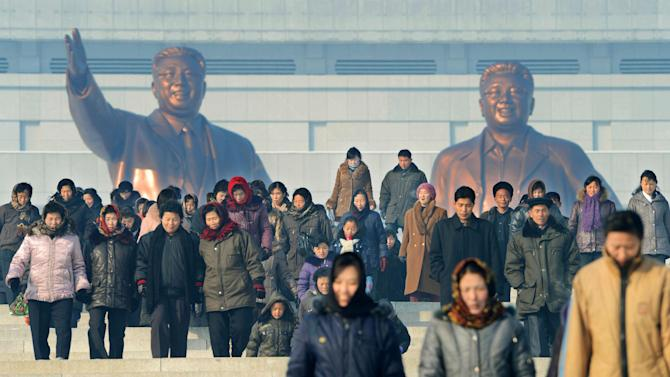 North Koreans walk after paying a visit to the bronze statues of national founder Kim Il Sung, left, and late leader Kim Jong Il on Mansu Hill in Pyongyang, North Korea Monday, Dec. 10, 2012. North Korea on Monday extended the launch period for a controversial long-range rocket by another week until Dec. 29, citing technical problems. (AP Photo/Kyodo News) JAPAN OUT, MANDATORY CREDIT, NO LICENSING IN CHINA, FRANCE, HONG KONG, JAPAN AND SOUTH KOREA
