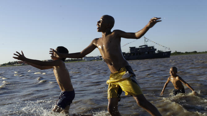 FILE - In this Oct. 14, 2012 file photo, children play in the water in Asuncion Bay, Paraguay. A poll released Wednesday of nearly 150,000 people around the world says seven of the world's 10 countries with the most upbeat attitudes are in Latin America. Gallup Inc. asked about 1,000 people in each of 148 countries last year if they were well-rested, had been treated with respect, smiled or laughed a lot, learned or did something interesting and felt feelings of enjoyment. In Panama and Paraguay, 85 percent of those polled said yes to all five, putting those countries at the top of the list. (AP Photo/Jorge Saenz, File)