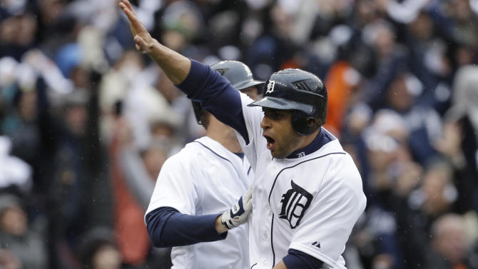 Detroit Tigers' Omar Infante high fives a teammate after scoring the game winning run on a sacrifice fly by teammate Don Kelly during the ninth inning of Game 2 of the American League division baseball series against the Oakland Athletics, Sunday, Oct. 7, 2012, in Detroit. (AP Photo/Paul Sancya)