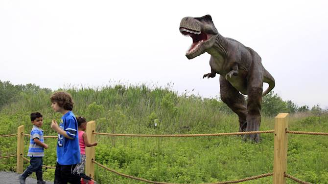 FILE - In this Friday, May 25, 2012 file photo, children stand near a life-size Tyrannosaurus Rex dinosaur model as it moves and growls in an interactive display at Field Station Dinosaurs in Secaucus, N.J. Scientists used to think T. rex stood tall, but they abandoned that idea decades ago. Now, the ferocious dinosaur is depicted in a bird-like posture, tail in the air and head pitched forward of its two massive legs. (AP Photo/MelEvans)