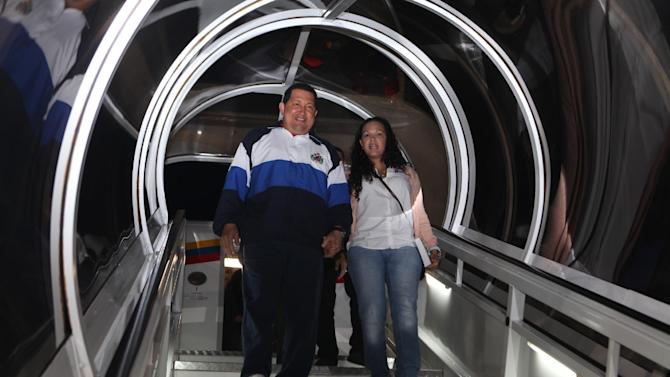 "CORRECTS NAME OF DAUGHTER TO VIRGINIA -- In this photo provided by Miraflores Presidential Press Office, Venezuela's President Hugo Chavez, left, accompanied by his daughter Rosa Virginia, smiles upon his arrival to Caracas, Venezuela, Wednesday April 11, 2012. Chavez returned to Venezuela and said he's ""doing well"" following cancer treatment in Cuba. Chavez flew to Cuba last week for his third round of radiation therapy. (AP Photo/Miraflores Presidential Office)"