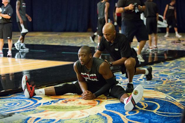 Miami Heat point guard Dwayne Wade stretches during a training camp session at the Atlantis Resort in Paradise Island, Bahamas, Tuesday, Oct. 1, 2013. The two-time defending NBA champions opened train