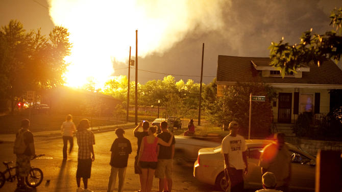 People watch the flames shoot up from a freight train that derailed and some cars burst into flames, early Wednesday morning July 11, 2012 in Columbus Ohio. Lt. Terry Bush says the accident happened at about 2 a.m. Wednesday in a mixed-use part of the city, and people living in one-mile radius of the blast have been evacuated. (AP Photo/Andrew Spear)