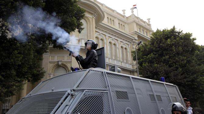 FILE - In this Sunday, Jan. 27, 2013 file photo, an Egyptian riot police officer fires a tear gas canister at protesters, not seen, during clashes near Tahrir Square, Cairo, Egypt. With near impunity and the backing of the Islamist president, Egyptian police have over the past week used excessive and often deadly force against protesters across much of the country, regaining their Mubarak-era notoriety as a tool of repression. With nearly 60 people dead and hundreds injured, police have re-emerged as a significant political player after spending the past two years on the sidelines. (AP Photo/Khalil Hamra, File)