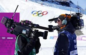 Media cameramen shouldering video cameras chat during the women's snowboard slopestyle qualifying round at the 2014 Sochi Olympic Games in Rosa Khutor
