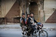 "Syrian rebel fighters ride a motorcycle in Maaret al-Numan in the northwestern province of Idlib, an area under the control of rebel fighters, on October 17. International peace envoy Lakhdar Brahimi has warned that the Syria conflict risks setting the region ""ablaze"", as clashes broke out across the border with Lebanon"