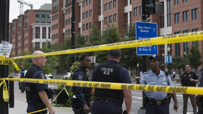 Police work the scene on M Street, SE in Washington near the Washington Navy Yard on Monday, Sept. 16, 2013. The U.S. Navy says one person is injured after a shooting at a Navy building in Washington. Police and emergency crews gathered Monday morning outside the Naval Sea Systems Command Headquarters building, where the shooting was reported. (AP Photo/Jacquelyn Martin)