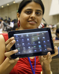 "An Indian student poses with the supercheap Aakash tablet computer which she received during its launch in New Delhi, India, Wednesday, Oct. 5, 2011. The $35 basic touch screen tablet aimed at students can be used for functions like word processing, web browsing and video conferencing. Aakash, manufactured by DataWind, has a 7"" Android 2.2 touch screen and a HD video coprocessor. The Indian government intends to deliver 10 million tablets to students across India. (AP Photo/Gurinder Osan)"
