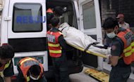 Pakistani rescuers carry a dead body after gunmen shot dead nine police prison staff on Thursday as they slept, the second attack on security forces in the country's political heartland since Islamabad reopened a NATO supply corridor