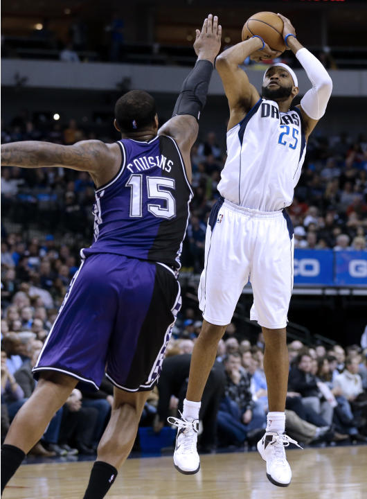 Dallas Mavericks' Vince Carter (25) shoots a 3-point basket as Sacramento Kings' DeMarcus Cousins (15) defends in the second half of an NBA basketball game Wednesday, Feb. 13, 2013, in Dallas. The Mav