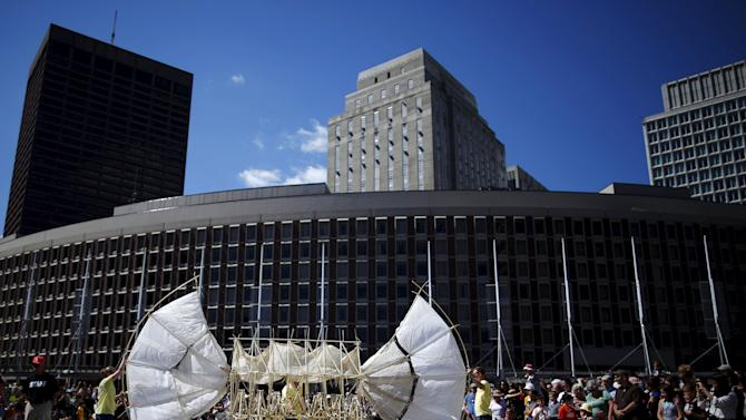 "Onlookers watch a display of ""Animaris Ordis,"" one from the series of ""Strandbeests"" kinetic sculptures by Dutch artist Theo Jansen, at City Hall Plaza in Boston, Massachusetts"