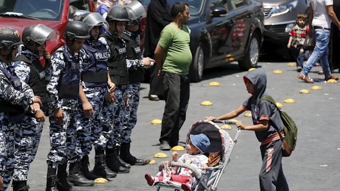 A boy pushes a baby stroller in front of policemen ahead of a protest in Amman