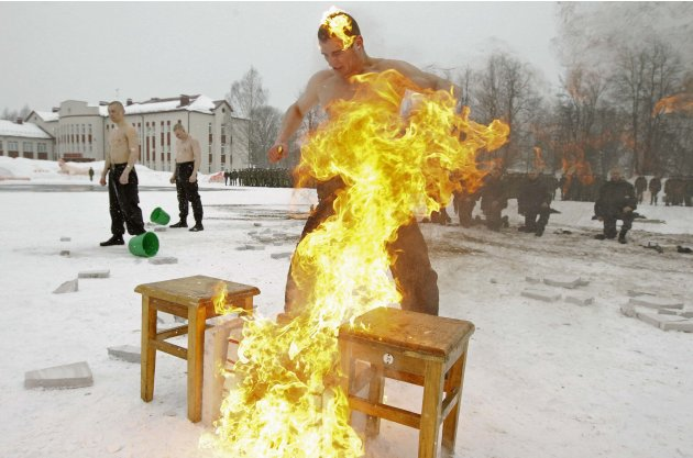 Serviceman of the Belarussian Interior Ministry's special forces unit breaks flaming tiles with his head during Maslenitsa celebrations at a base in Minsk