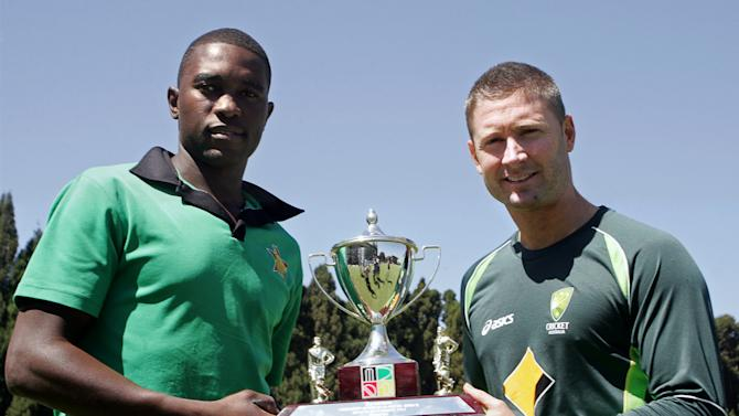 Zimbabwe captain Elton Chigumbura (L) holds the triangular series trophy with Australian counterpart Michael Clarke ahead of the tri-series including South Africa at the Harare Sports Club on August 24, 2014