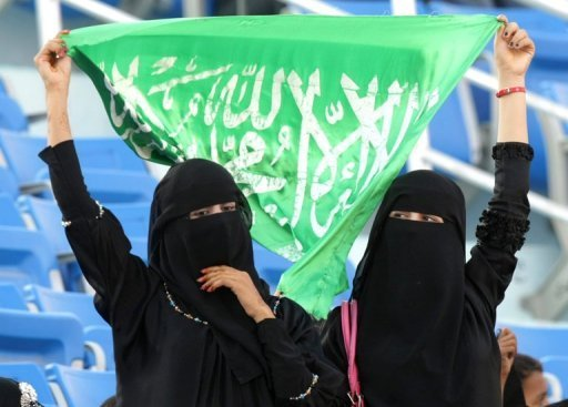 <p>Saudi women hold up their national flag as they watch the opening ceremony of the Gulf Cup in the southern Yemeni city of Aden on November 2010. Two female athletes from Saudi Arabia will compete at the London Games this summer in a historic first for the country, the International Olympic Committee said on Thursday.</p>
