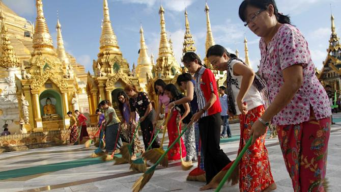 In this Aug. 17, 2014 photo, a group of Buddhist devotees sweep on platform at Myanmar famous Shwedagon Pagoda in Yangon, Myanmar. Every evening, more than a dozen men and women walk in a tight row in front of Myanmar's most revered Buddhist pagoda, sweeping the vast marble terrace in unison in hopes of keeping it clean for barefoot pilgrims. To these volunteers, this is not a chore but a noble act, one they carry out eagerly in an effort to gain merit, or spiritual credit. (AP Photo/Khin Maung Win)