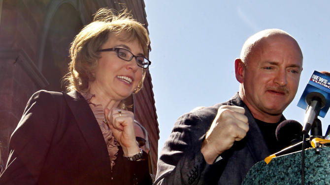 """Former Rep. Gabrielle Giffords, left, shouts """"fight, fight, fight"""" as she and husband,  Mark Kelly,  pump their fists together as they returned to the site of a shooting that left Giffords critically wounded on Wednesday, March 6, 2013, in Tucson, Ariz.  Giffords urged senators to pass background checks for gun purchases.  (AP Photo/Ross D. Franklin)"""