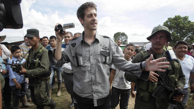 French journalist Romeo Langlois, center, is escorted by rebels of the Revolutionary Armed Forces of Colombia, FARC, upon their arrival to San Isidro, southern Colombia, Wednesday, May 30, 2012. Langlois , who was taken by rebels on April 28 when they attacked troops he was accompanying on a cocaine-lab eradication mission, was handed over by the rebels to a delegation that included a French diplomat in San Isidro. (AP Photo/Fernando Vergara)