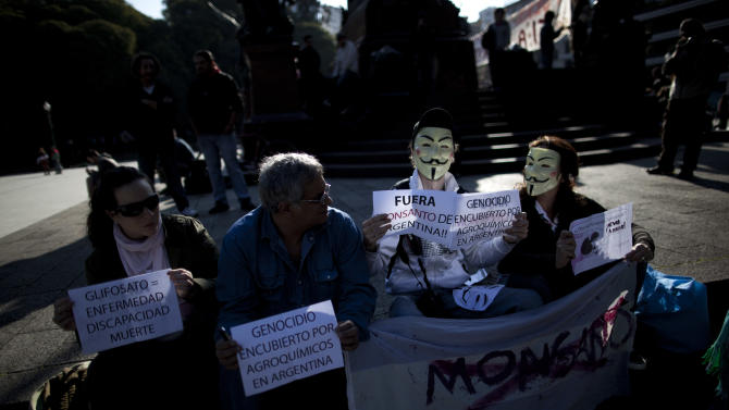 "Demonstrators hold signs reading in Spanish ""Glyphosate = illness, disability, death,"" left, ""Genocide concealed by agrochemicals in Argentina,"" second from left, and ""Get out Monsanto from Argentina"" near the offices of the U.S.-based company Monsanto in Buenos Aires, Argentina, Saturday, May 25, 2013. Activists are taking part in a global protest ""March Against Monsanto"" against the seed giant, demanding a stop to the use of agrochemicals and the production of genetically modified food. Protesters say genetically modified organisms can lead to serious health conditions and harm the environment. (AP Photo/Natacha Pisarenko)"