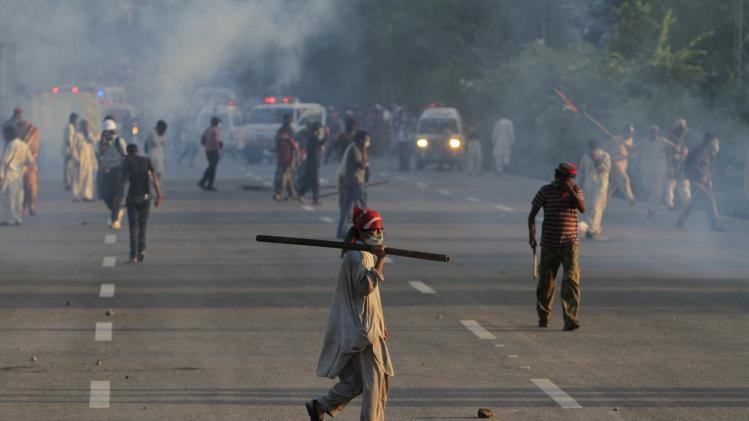 Anti-government protesters clash with riot police during the Revolution March in Islamabad