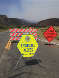 Highway 14 north of Laporte Colo., is closed to motorists on Sunday, June 17, 2012, as a stubborn wildfire continues to burn in northern Colorado. Crews are facing powerful winds as they battle the blaze that has scorched about 86 square miles of mountainous forest land and destroyed at least 181 homes, the most in state history. (AP Photo/David Zalubowski)