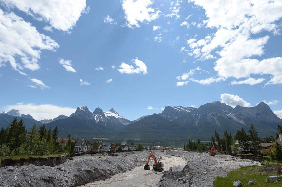 Excavators work on the Cougar Creek bed in Canmore, Alberta, Canada on Saturday, June 22, 2013 after flooding which devastated much of southern Alberta province. (AP Photo/The Canadian Press, Jonathan Hayward)