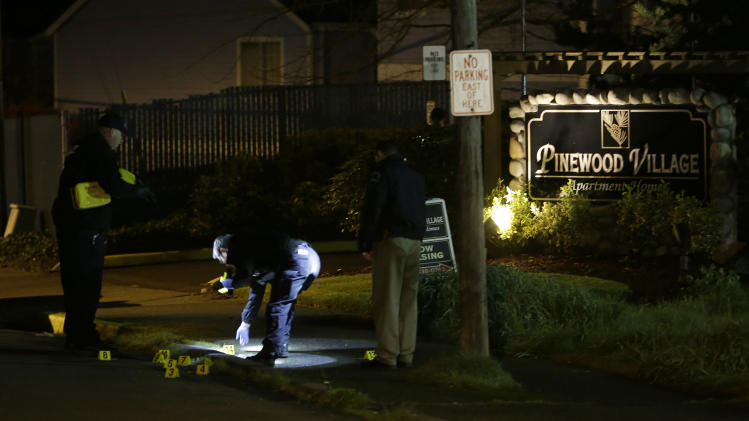 Police officers place evidence markers at the scene of an overnight shooting that left five people dead, Monday, April 22, 2013, at the Pinewood Village apartment complex in Federal Way, Wash. (AP Photo/Ted S. Warren)