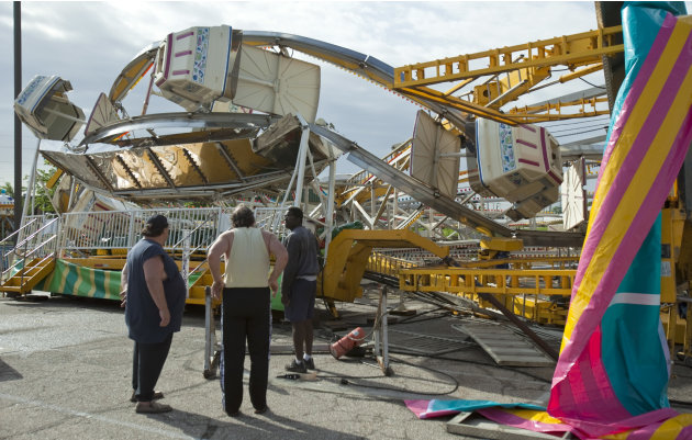 Ottaway Amusement, Inc. workers survey the damage to a 65-foot tall Ferris wheel Sunday morning, April 15, 2012, that toppled over onto another ride at Kellogg and Greenwicht following a tornado that