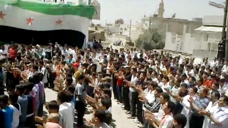 In this image made from amateur video released by the Shaam News Network and accessed Wednesday, May 23, 2012, purports to show Syrians chanting slogans during a demonstration in Idlib, Syria. (AP Photo/Shaam News Network via AP video) TV OUT, THE ASSOCIATED PRESS CANNOT INDEPENDENTLY VERIFY THE CONTENT, DATE, LOCATION OR AUTHENTICITY OF THIS MATERIAL