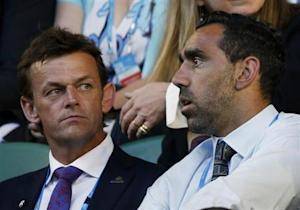 Australian cricketer Gilchrist sits with AFL player Goodes the spectator stands ahead of men's singles final match at the Australian Open 2014 tennis tournament in Melbourne