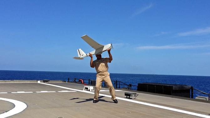 U.S. Navy Rear Admiral Sinclair Harris prepares lo launch a UAS (unmanned aircraft system) named Puma from the deck of his high speed vessel Swift near Key West, Florida, Friday, April 26, 2013. The U.S. Navy on Friday began testing two new aerial tools, borrowed from the battlefields of Afghanistan and Iraq, that officials say will make it easier to detect, track and videotape drug smugglers in action. (AP Photo/Ben Fox)