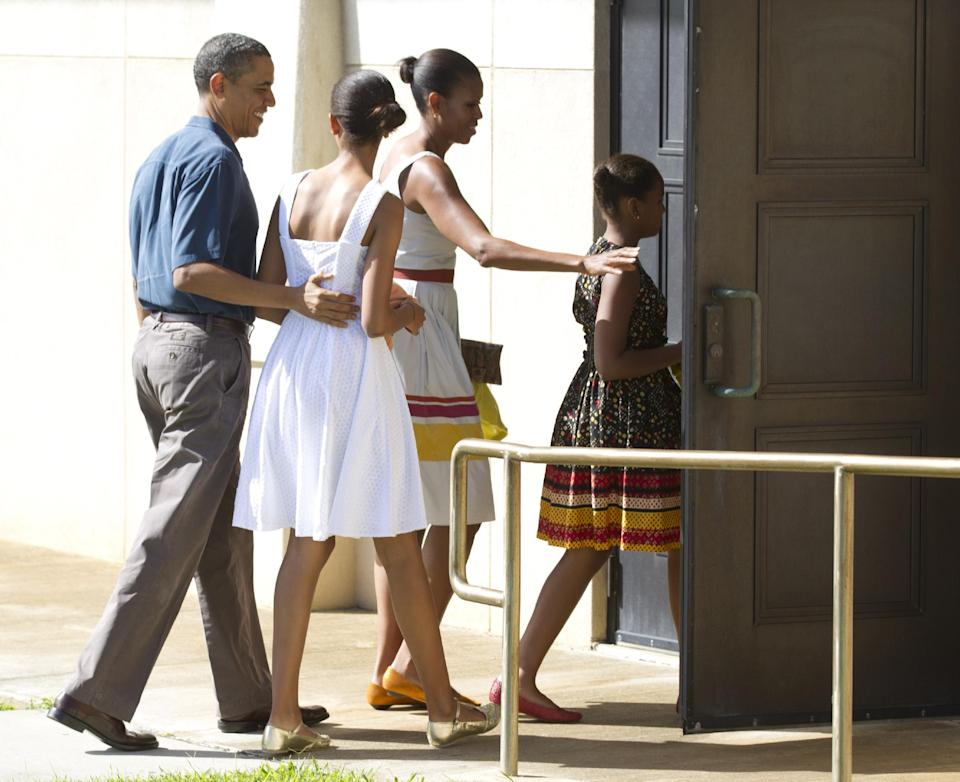President Barack Obama, first lady Michelle Obama and their daughters Malia and Sasha arrive to attend Christmas service at the Kaneohe bay Chapel on Marine Corps Base Hawaii, Sunday, Dec. 25, 2011, in Kaneohe, Hawaii. (AP Photo/Carolyn Kaster)