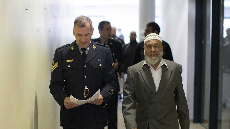 Royal Canadian Mounted Police Sgt. Laporte walks with Mohammad Shaied Sheikh of the Masjid el Noor Mosque before attending a news conference in Toronto, Monday, April 22, 2013, as the Royal Canadian Mounted Police announce the arrest of two men accused of plotting a terror attack on rail target. (AP Photo/The Canadian Press, Chris Young)