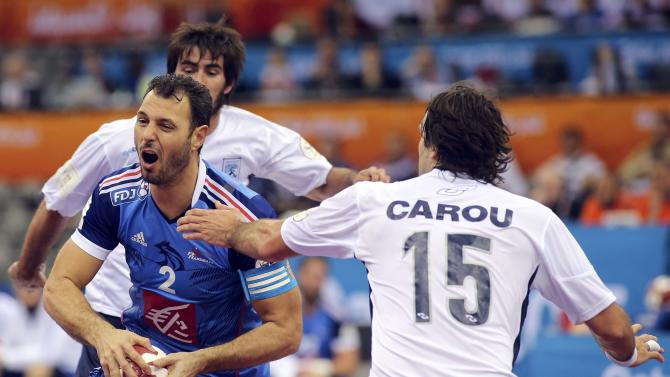 Jerome Fernandez of France is blocked by Carou of Argentina during their round of 16 match of the 24th men's handball World Championship in Doha