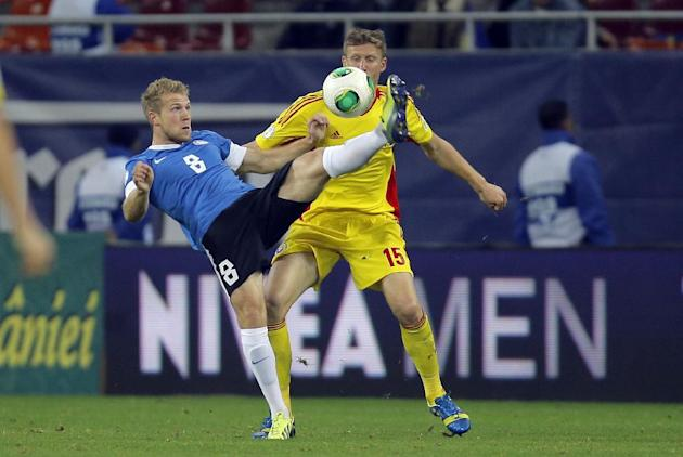 Henri Anier, left, of Estonia and Dorin Goian, right, of Romania challenge for the ball during the World Cup Group D qualifying soccer match at the National Arena stadium in Bucharest, Romania, Tuesda