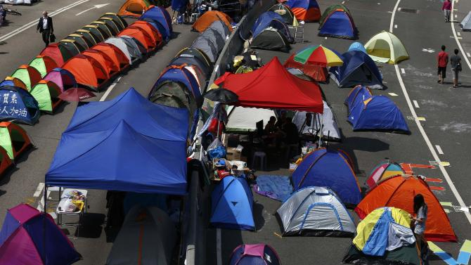 """People walk past a """"tent city"""", with hundreds of tents set up by pro-democracy protesters blocking a main road leading to the financial Central district in Hong Kong"""