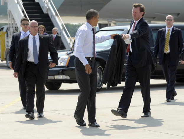 President Barack Obama passes his jacket to White House Trip Director Marvin Nicholson before heading over to greet people after arriving at Northern Kentucky International Airport in Boone, Ky., Monday, July 16, 2012. Obama is spending the day campaigning in Cincinnati. (AP Photo/Susan Walsh)