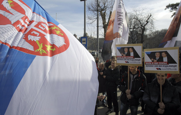A protester waves a Serbian flag during the protest in front of the presidency building in Belgrade, Serbia, Tuesday, Feb. 5, 2013. Dozens of ultranationalists have accused Serbia's president of treas