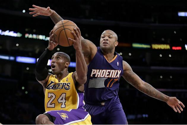 Los Angeles Lakers guard Kobe Bryant, left, drives to the basket past Phoenix Suns forward P.J. Tucker during the first half of an NBA basketball game in Los Angeles, Tuesday, Dec. 10, 2013