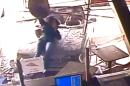 In this image from surveillance camera video, a female pedestrian is carried on the hood of a vehicle as it crashes through the glass front entrance of a Pudge Brothers Pizza shop in Aurora, Colo. on Wednesday, March 11, 2015. After the vehicle came to a stop, she immediately hopped off the car amid debris and escaped serious injury. (AP Photo/Pudge Brothers Pizza)
