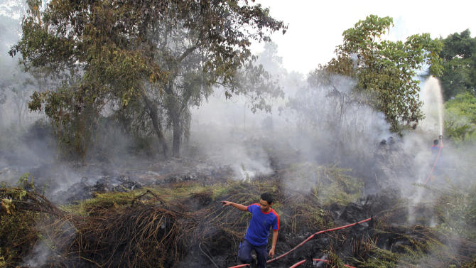 Firemen spray water to extinguish a bushfire in Pekanbaru, Riau province, Indonesia, Friday, June 21, 2013. The blazes in peat swamp forests on Indonesia's Sumatra island have sent massive plumes of smog across the sea to neighboring Singapore and Malaysia, both of which have grown impatient with Indonesia's response to the problem that occurs nearly every year. (AP Photo/Rony Muharrman)